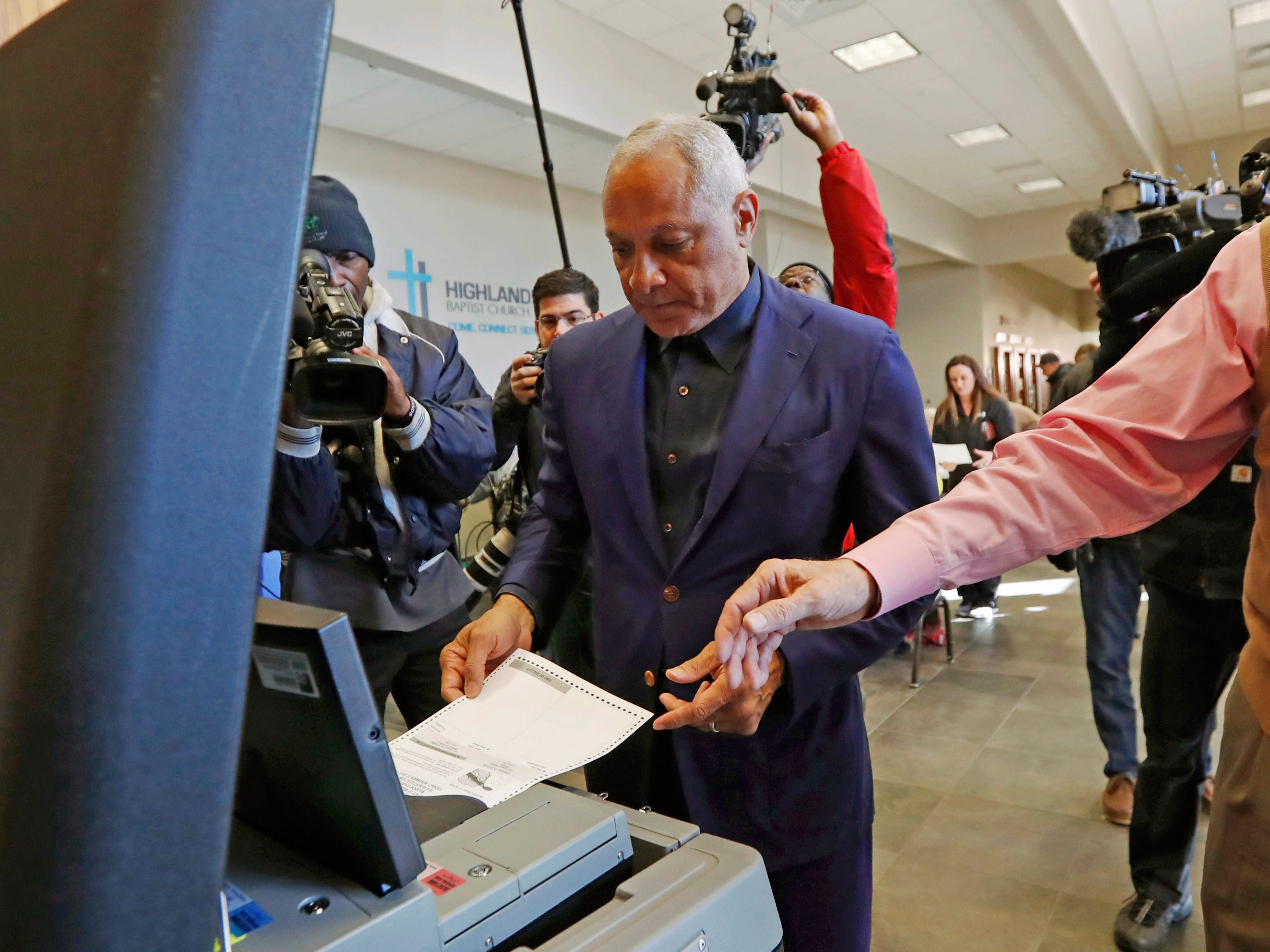 Democrat Mike Espy, left feeds his ballot into the submission machine, as directed by poll manager Larry Greer, Tuesday, Nov. 27, 2018 in Ridgeland, Miss. Mississippi voters are deciding the last U.S. Senate race of the midterms, choosing between Espy and Republican Sen. Cindy Hyde-Smith.