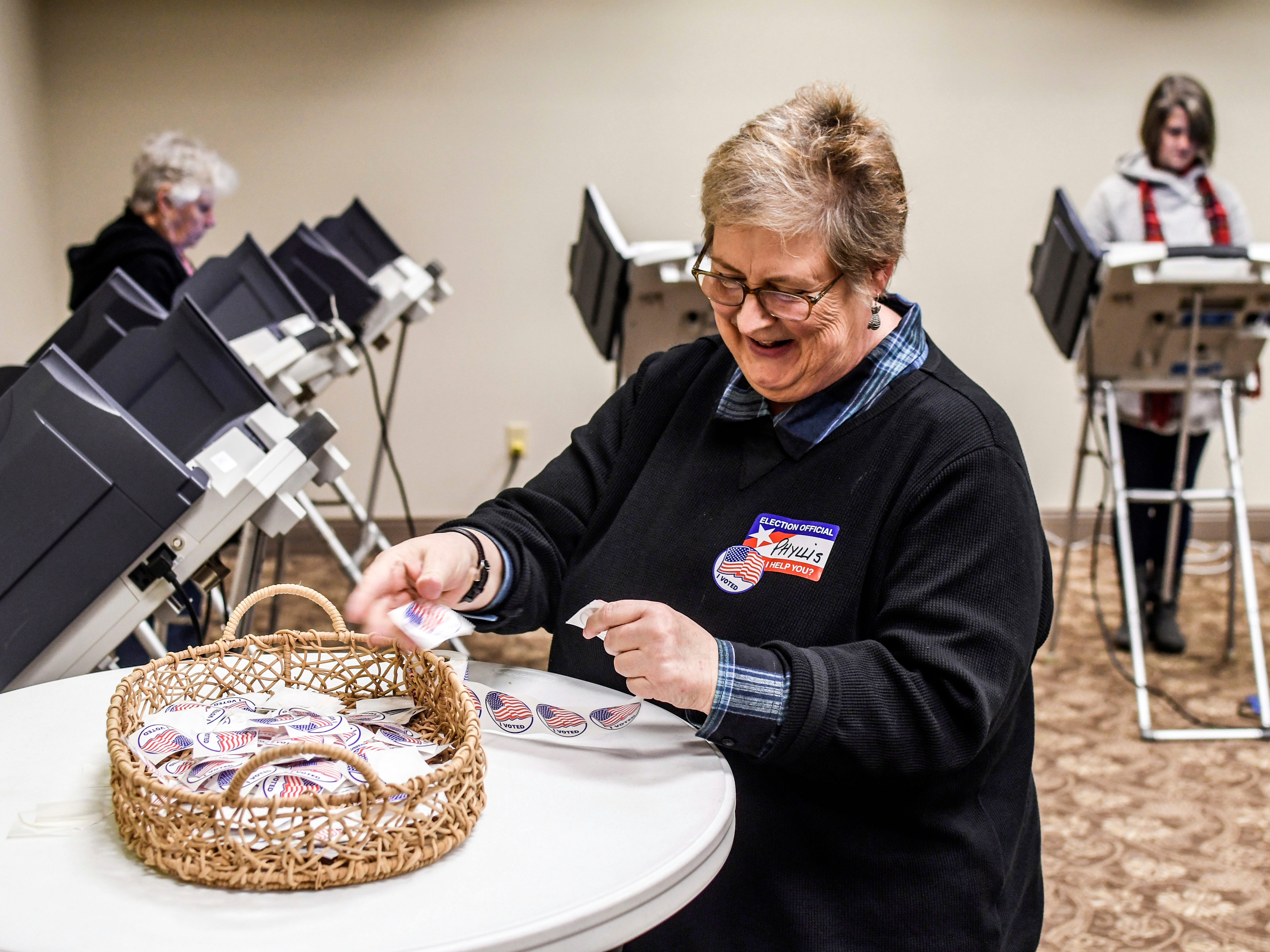 "Poll worker Phyllis Johnson puts stickers that read ""I Voted"" in a basket at a table at the polls at the Oxford Conference Center in Oxford, Miss. on Tuesday, Nov. 27, 2018. Mississippi voters are deciding the last U.S. Senate race of the midterms, choosing between Espy and Republican Sen. Cindy Hyde-Smith."