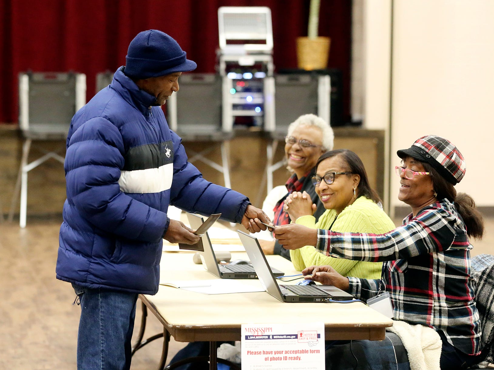 L.M. Walker  shows his identification to vote in a runoff election Tuesday, Nov. 27, 2018 in Gulfport, Miss.  Mississippi voters are deciding the last U.S. Senate race of the midterms, choosing between Democrat Mike Espy and Republican Sen. Cindy Hyde-Smith.