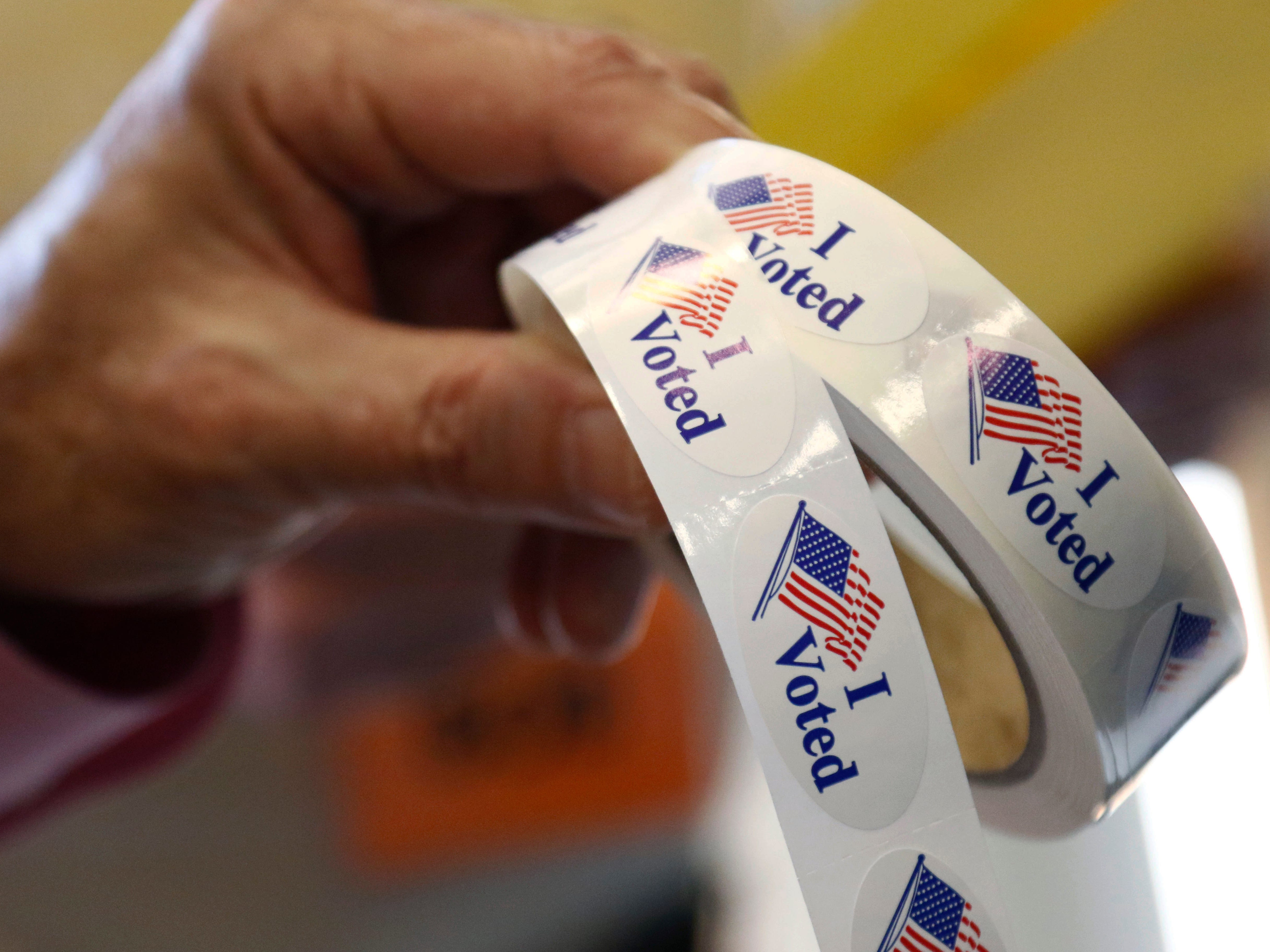 """Poll manager Larry Greer hands holds a roll of """"I Voted"""" stickers given each person after voting in a runoff election Tuesday, Nov. 27, 2018 in Ridgeland, Miss.  Mississippi voters are deciding the last U.S. Senate race of the midterms, choosing between Espy and Republican Sen. Cindy Hyde-Smith."""