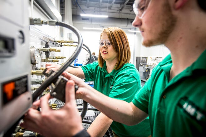 Asia Ricketts and AMT cohort James Box practice skills on a pneumatics trainer in a engineering systems lab at JSCC.