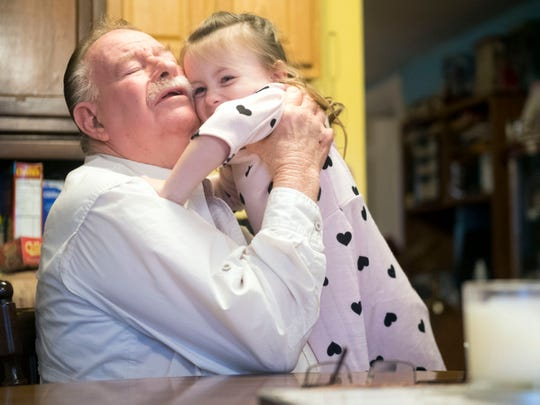 """Cecil Brown picks up his granddaughter Hope for a hug at their home Tuesday, Nov. 20, 2018. Cecil and his wife, Donna, are raising Hope, but face many physical challenges because of their health. """"If she wasn't such a good baby, we probably couldn't have done it,"""" he said. The family is receiving an Empty Stocking Fund basket to help during the holidays."""