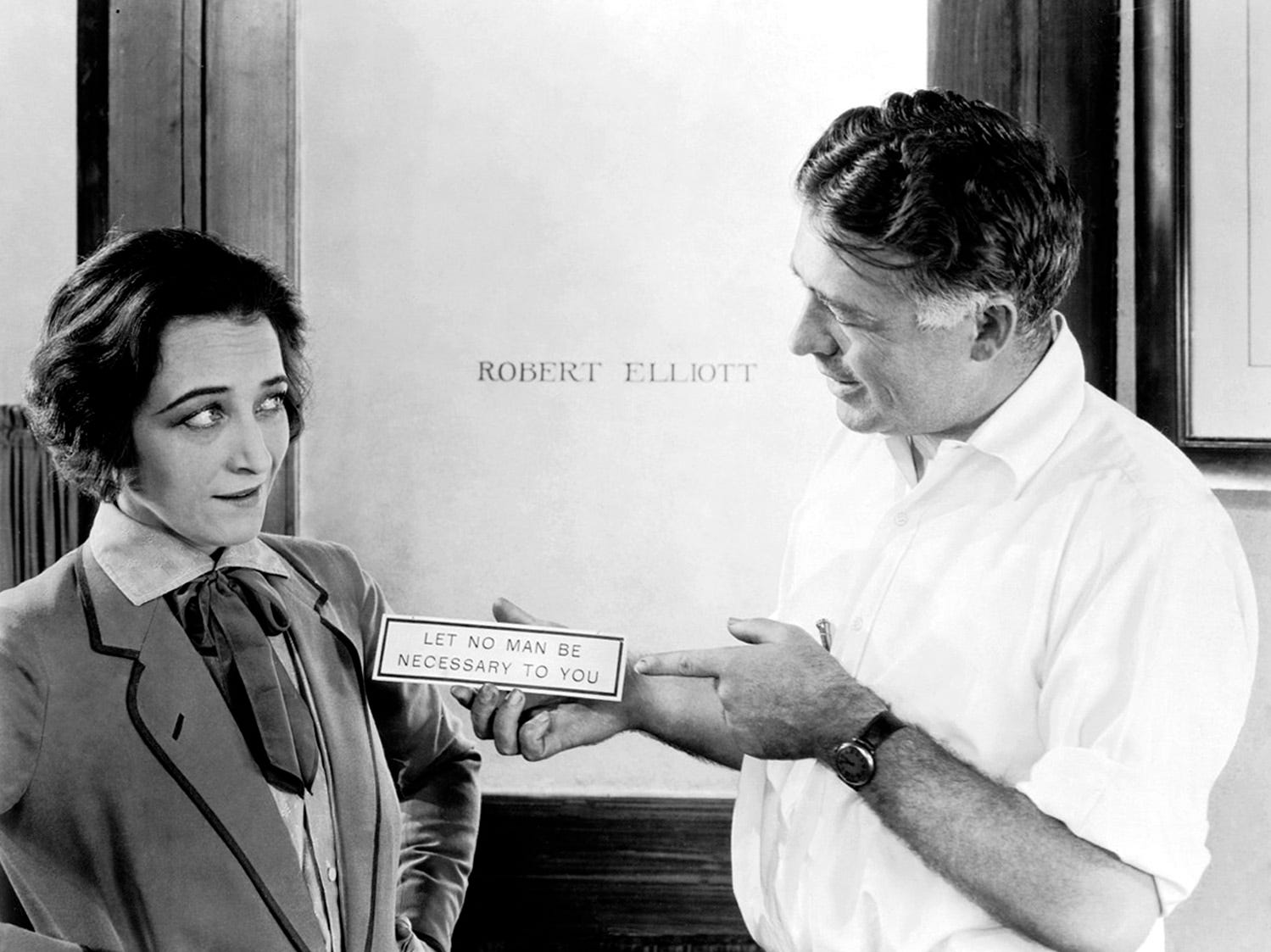 1925: Director Clarence Brown (1890 - 1987) presents a plaque to actress Pauline Frederick (1883 - 1938) on the set of 'Smouldering Fires', in front of Robert Elliott's office door. The plaque reads 'Let No Man Be Necessary To You'.