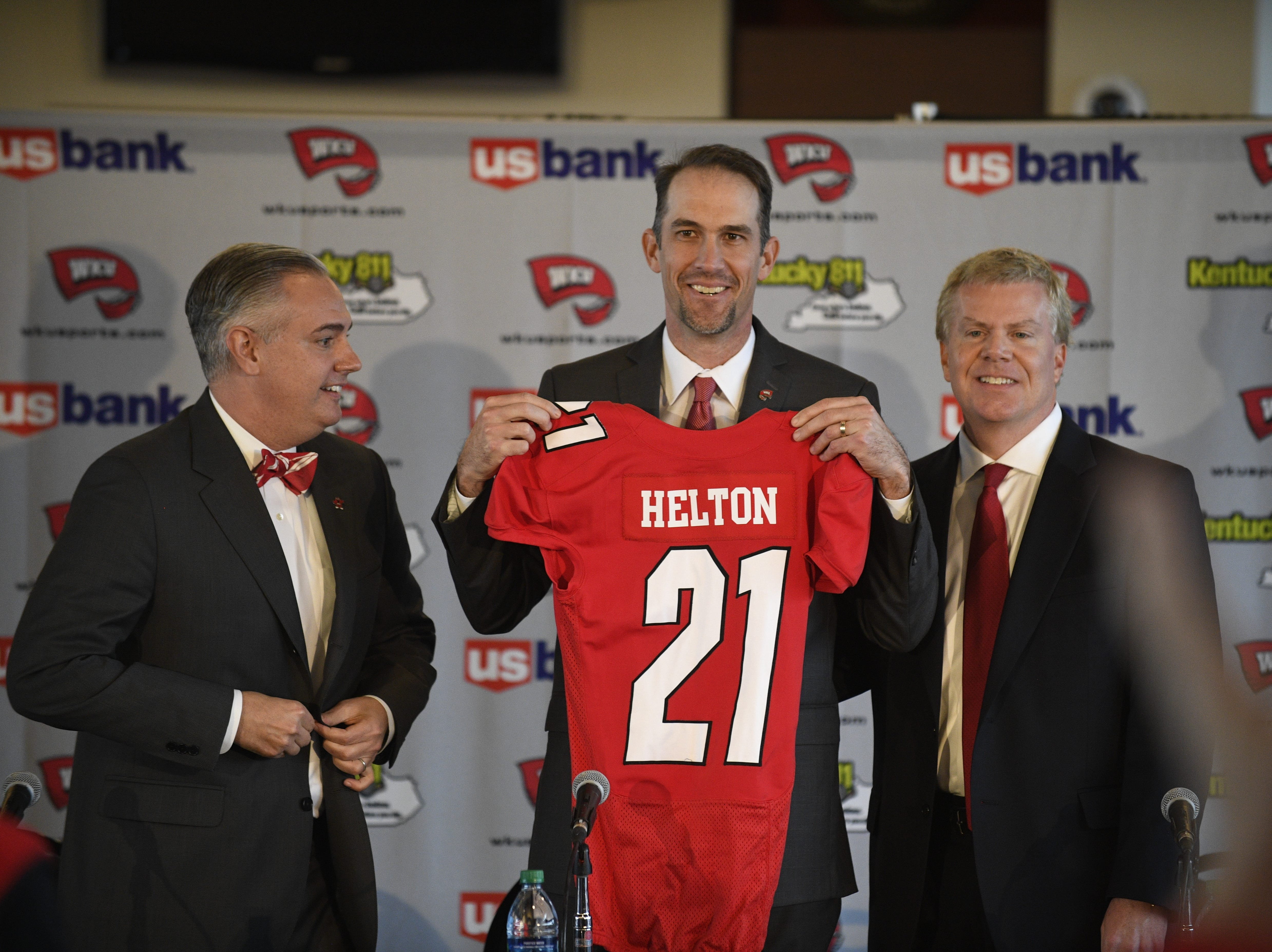 Western Kentucky's new head football coach Tyson Helton, center, holds up a jersey as WKU president Tim Caboni, left, and athletic director Todd Stewart, right,  pose for a photo at the NCAA college football press conference, Tuesday, Nov. 27, 2018, at the Jack and Jackie Harbaugh Stadium Club at Houchens-Smith Stadium in Bowling Green, Ky.