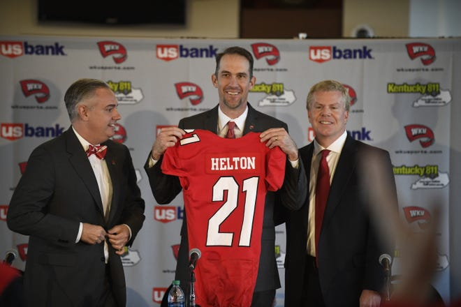 Western Kentucky's new football coach, Tyson Helton, center, holds up a jersey as WKU President Tim Caboni, left, and athletics director Todd Stewart, right, pose for a photo at a press conference Nov. 27.
