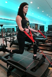 Lacey Barr, co-owner of the new Core Change in Turkey Creek, demonstrates a routine Tuesday, Nov. 27, 2018. Core Change, has brought the Lagree workout to the Knoxville market with the Megaformer machine. It's a low-impact, high intensity workout.