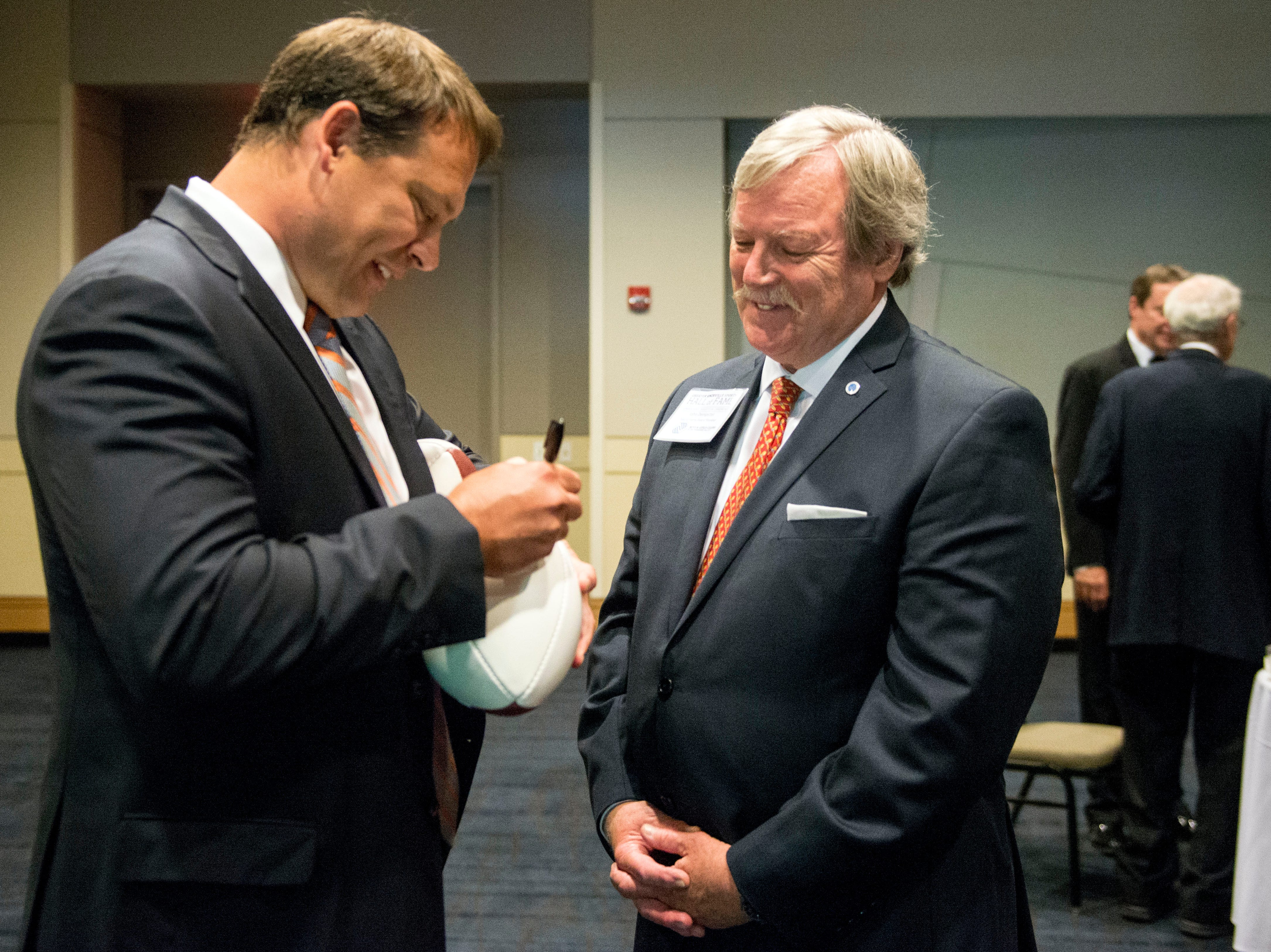 Former Tennessee quarterback and North Carolina congressman Heath Shuler signs a football for John Dempster during a reception before the Greater Knoxville Sports Hall of Fame Dinner and Induction Ceremony at the Knoxville Convention Center on Tuesday, July 26, 2016. (SAUL YOUNG/NEWS SENTINEL)