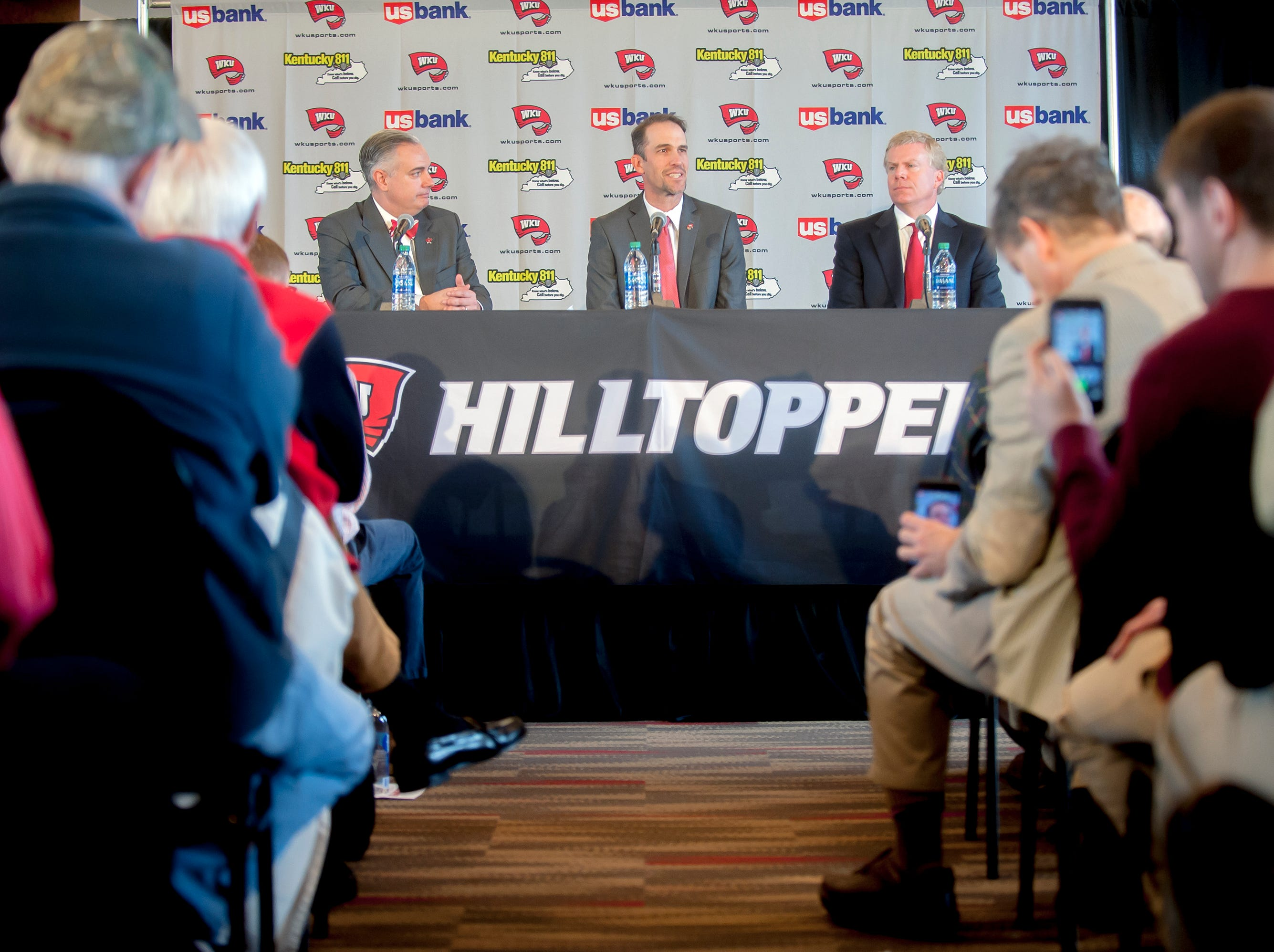 Western Kentucky's new head football coach Tyson Helton center, speaks as WKU president Tim Caboni, left, and athletic director Todd Stewart, right,  listen during an NCAA college football press conference, Tuesday, Nov. 27, 2018, at the Jack and Jackie Harbaugh Stadium Club at Houchens-Smith Stadium in Bowling Green, Ky.