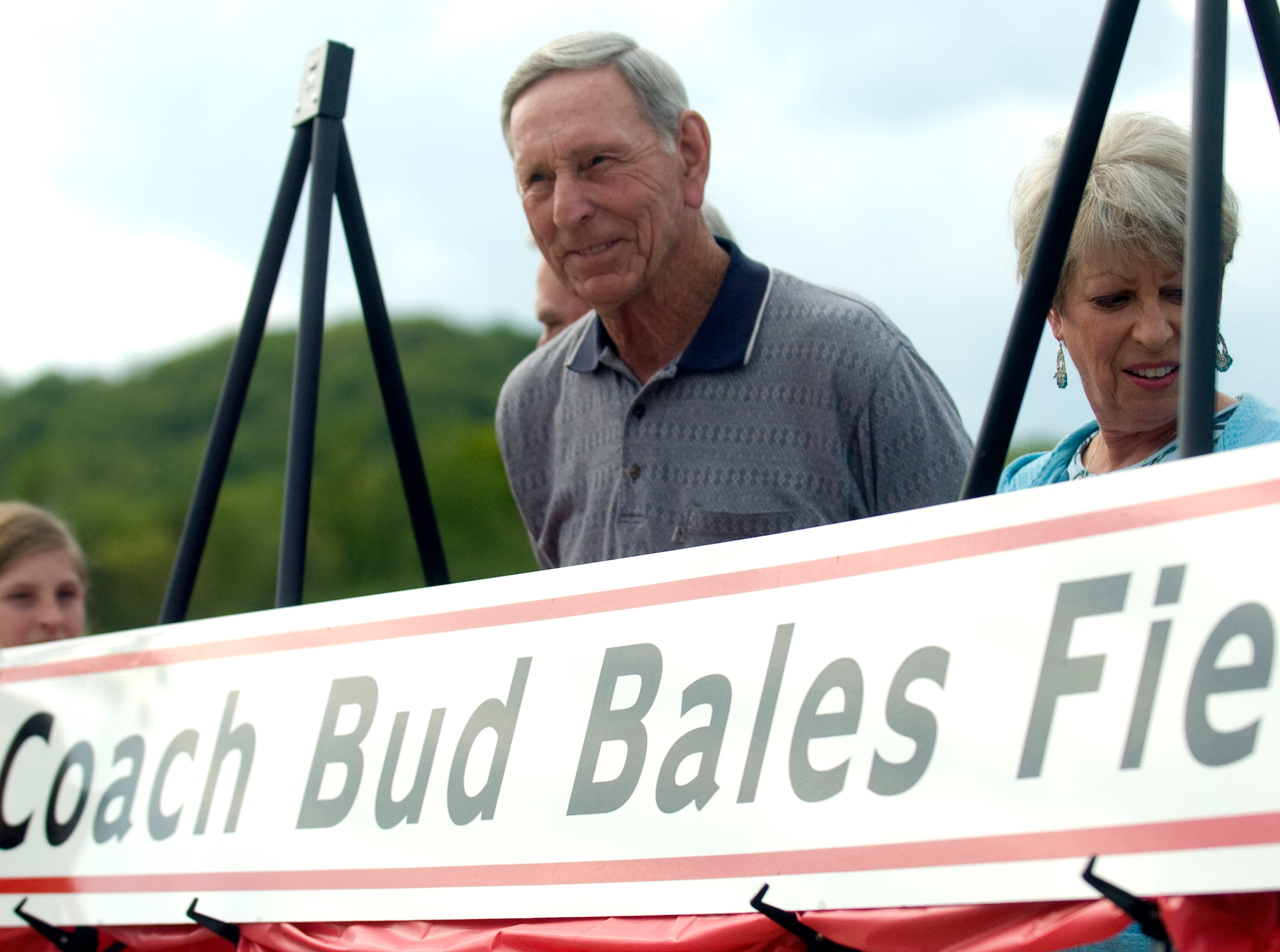 Bud Bales smiles as he stands behind the sign that will decorate a baseball field at Tommy Schumpert Park in his honor. Bales served as Central's head baseball coach fro 1974 to 2000. Central High School and Halls square off in baseball at Tommy Schumpert Park on Central's new Bud Bales Field on Wednesday, Apr. 21, 2010.