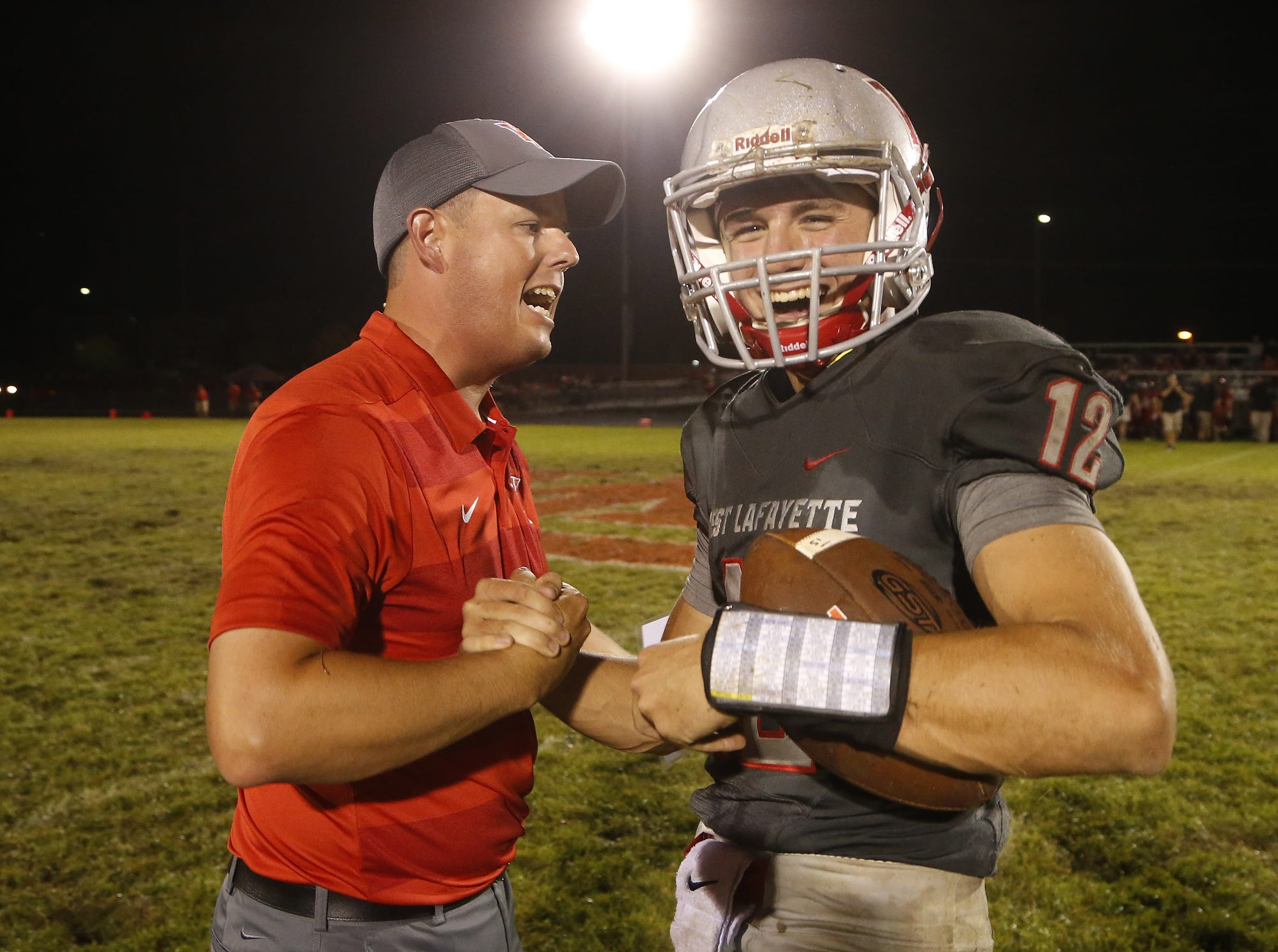 West Lafayette head coach Shane Fry celebrates with quarterback Kyle Adams after the Red Devils defeated Lafayette Jeff 38-29 Friday, August 17, 2018, at Gordon Straley Field in West Lafayette.