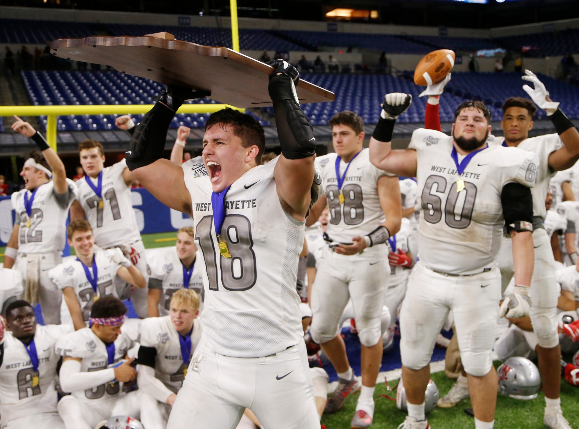 Sage Hood of West Lafayette hoists the Class 3A state title trophy after the Red Devils defeated  Evansville Memorial 47-42 in the Class 3A State Championship Saturday, November 24, 2018, at Lucas Oil Stadium in Indianapolis.