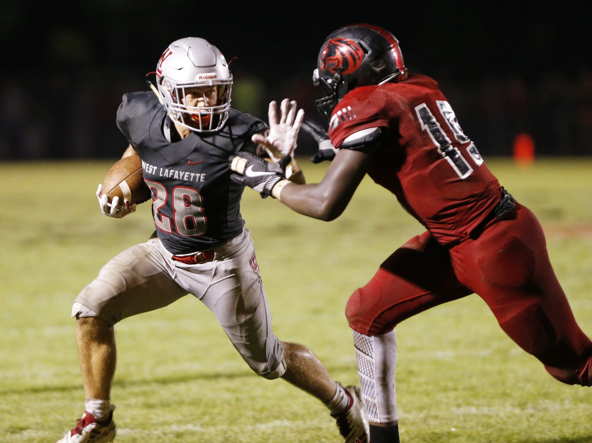 Spencer Blankman of West Lafayette with a stiff arm for Xavier Detrick on a carry Friday, August 17, 2018, at Gordon Straley Field in West Lafayette. West Lafayette defeated Jeff 38-29.