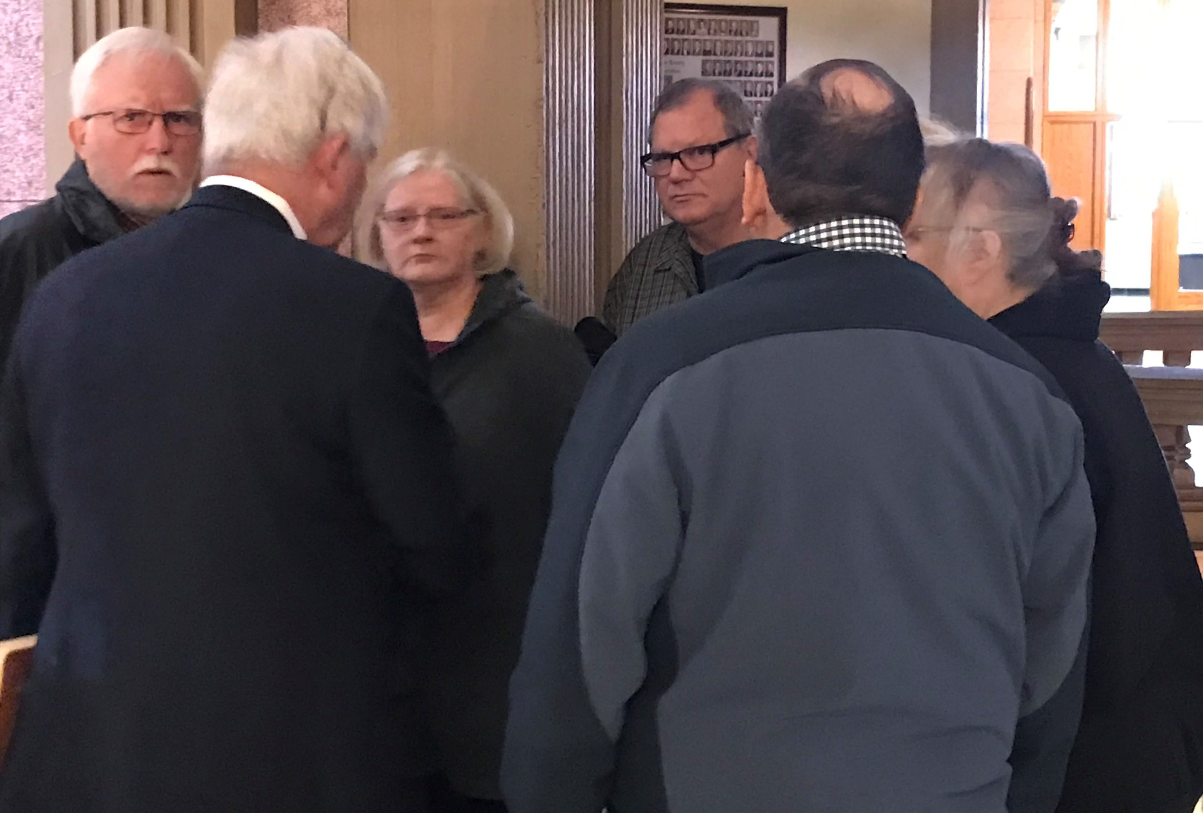 Laura Hettinger, center, meets with her supporters and her attorney after she was sentenced for stealing $471,222 from her employer.