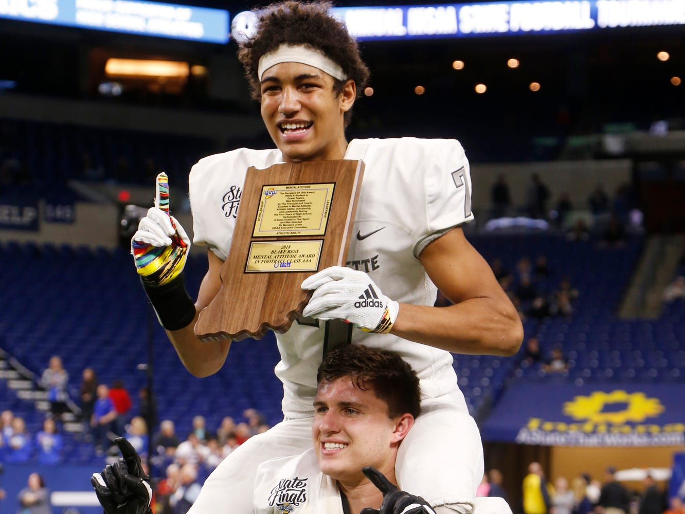Sage Hood of West Lafayette lifts teammate Kyle Hazell onto his shoulders after Hazell was named the mental attituted award winner for Class 3A following the Red Devils 47-42 victory over Evansville Memorial in the Class 3A State Championship Saturday, November 24, 2018, at Lucas Oil Stadium in Indianapolis.