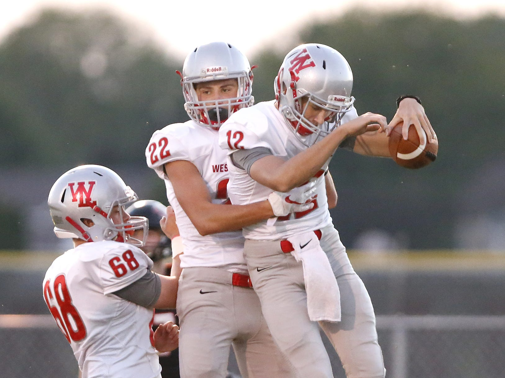 West Lafayette quarterback Kyle Adams, right,  celebrates with teammates R. J. Erb and Joey Gavin after rushing for a touchdown at 10:58in the first quarter against Rensselaer Friday, September 14, 2018, in Rensselaer. West Lafayette defeated Rensselaer 69-14.