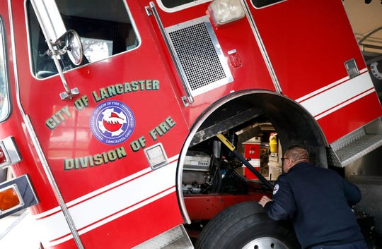 Lancaster Fire Capt. Brian Archer looks under the cab of the department's 1994 mini tower truck Tuesday, Nov. 27, 2018, at Engine House 1 in downtown Lancaster. The truck is currently the department's only reserve engine. When firefighters tried to drive the truck out of the station for a photograph Tuesday they discovered they couldn't shift it out of park. Monday night the department asked city council to approve the purchase of a new fire engine that would rotate with the city's other fire trucks to decrease wear on all the equipment.