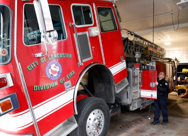 Lancaster Fire Capt. Brian Archer tips the cab of the department's 1994 mini tower truck Tuesday, Nov. 27, 2018, at Engine House 1 in downtown Lancaster. The truck is currently the department's only reserve engine. When firefighters tried to drive the truck out of the station for a photograph Tuesday they discovered they couldn't shift it out of park. Monday night the department asked city council to approve the purchase of a new fire engine that would rotate with the city's other fire trucks to decrease wear on all the equipment.