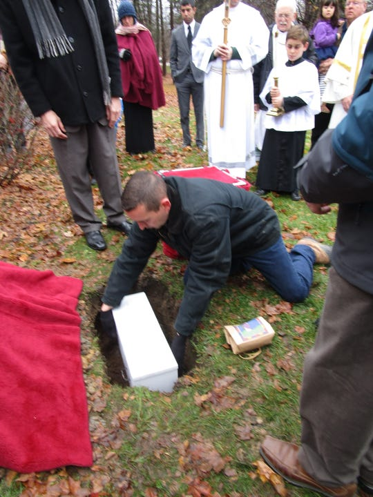 A man places into the ground a coffin containing what pro-life activists say is a 7-week-old aborted fetus as mourners watch at the Holy Spirit Roman Catholic Cemetery in Brighton on Nov. 24, 2018.