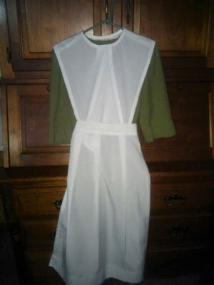 A dress ready for a wedding showing cape, apron, and basic dress.