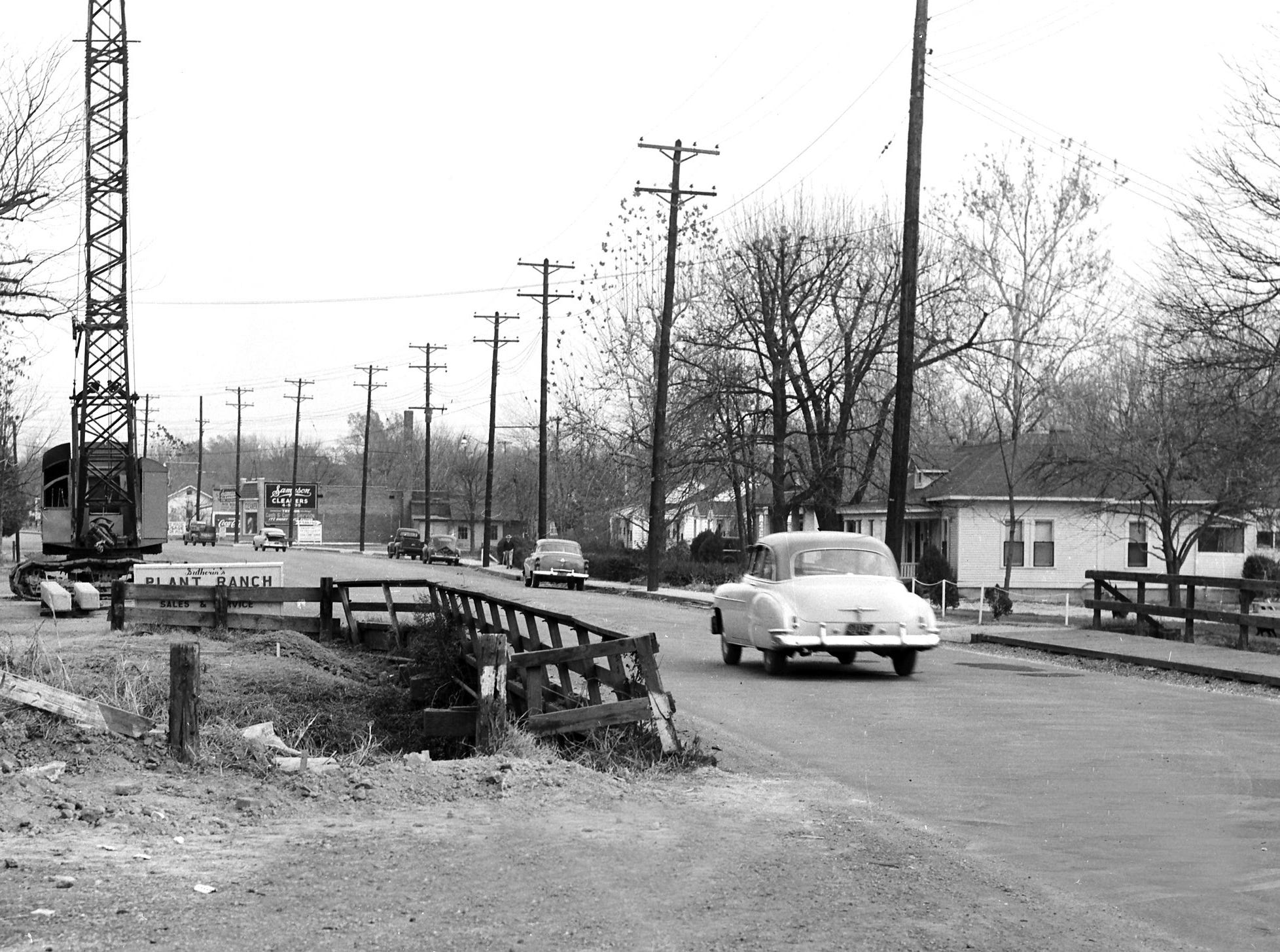 City Engineering Department crews conduct pile boring tests on 8 Dec 1954, preliminary to widening a bridge in the 3300 block of Broad in order to convert the street into a through street from East Parkway to Summer at National.  Improvement is expected to divert a large volume of traffic from Summer west of National.  The expanded part of the bridge will be of steel and concrete construction.