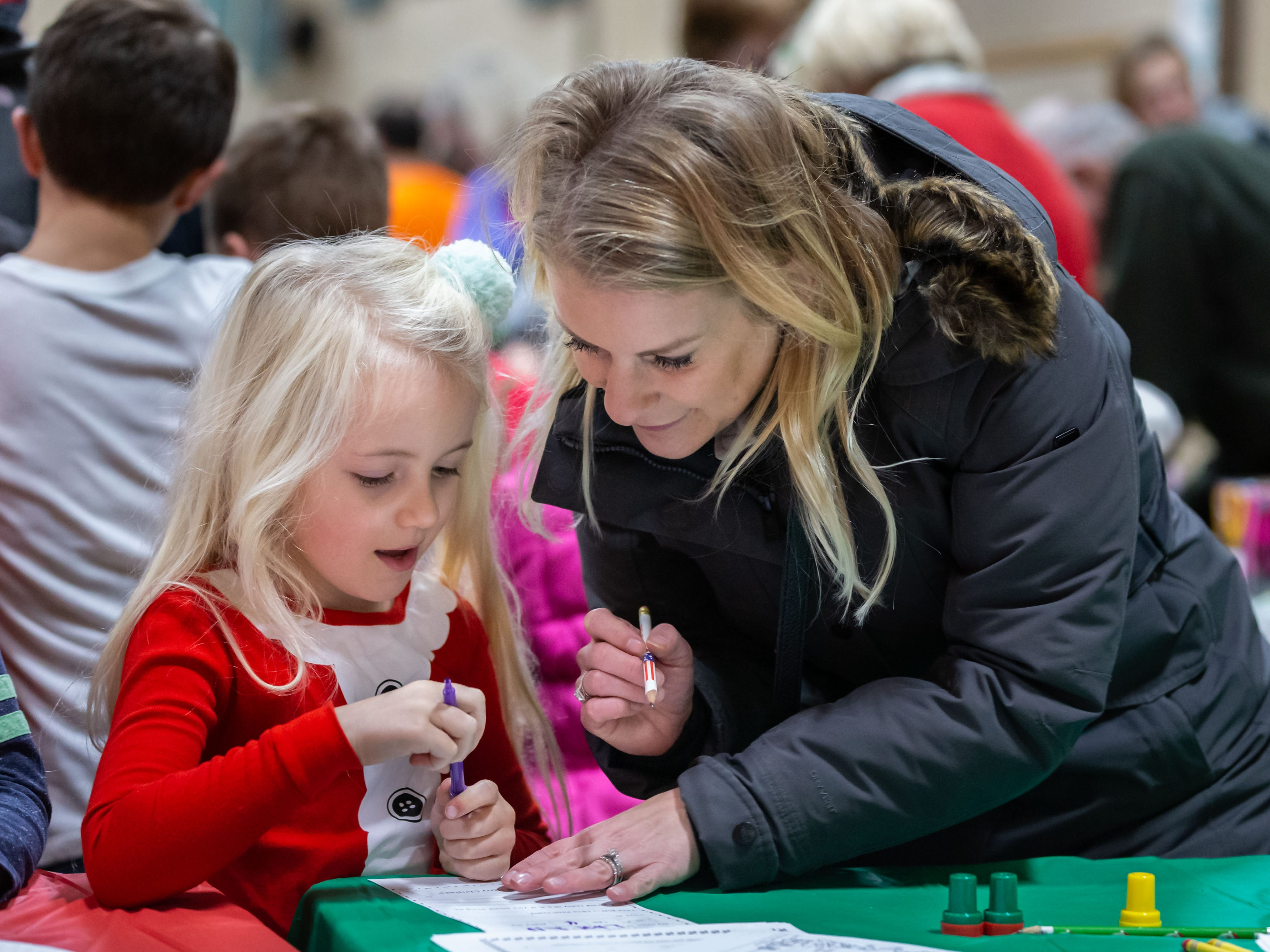 Sarah Fitting of Cedarburg helps four-year-old Lauren Dykstra write a letter to Santa during Cedarburg's annual tree lighting ceremony at the Community Center on Monday, Nov. 26, 2018. The event, hosted by Cedarburg Chamber of Commerce, features make-and-take crafts, cookies, cider, music, caroling and a visit from Santa to light the tree.