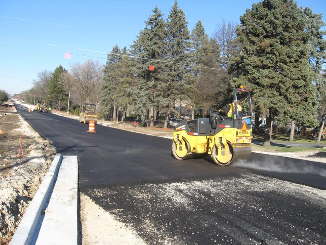 The fresh asphalt steams off the newly paved 124th Street as work crews hurry to finish by winter. They didn't make it, however, and will have to give the road a final layer of asphalt next spring.