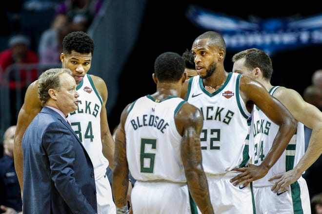 Bucks coach Mike Budenholzer (left) wasn't happy with the defensive effort of forward Khris Middleton (22) on Saturday night.