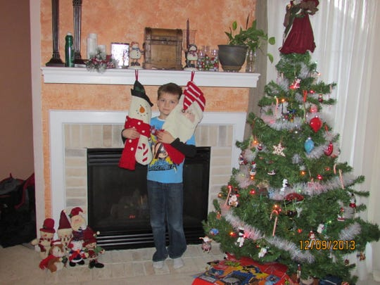 Kathie Devlin's son hangs stockings on the mantel in preparation for St. Nick.