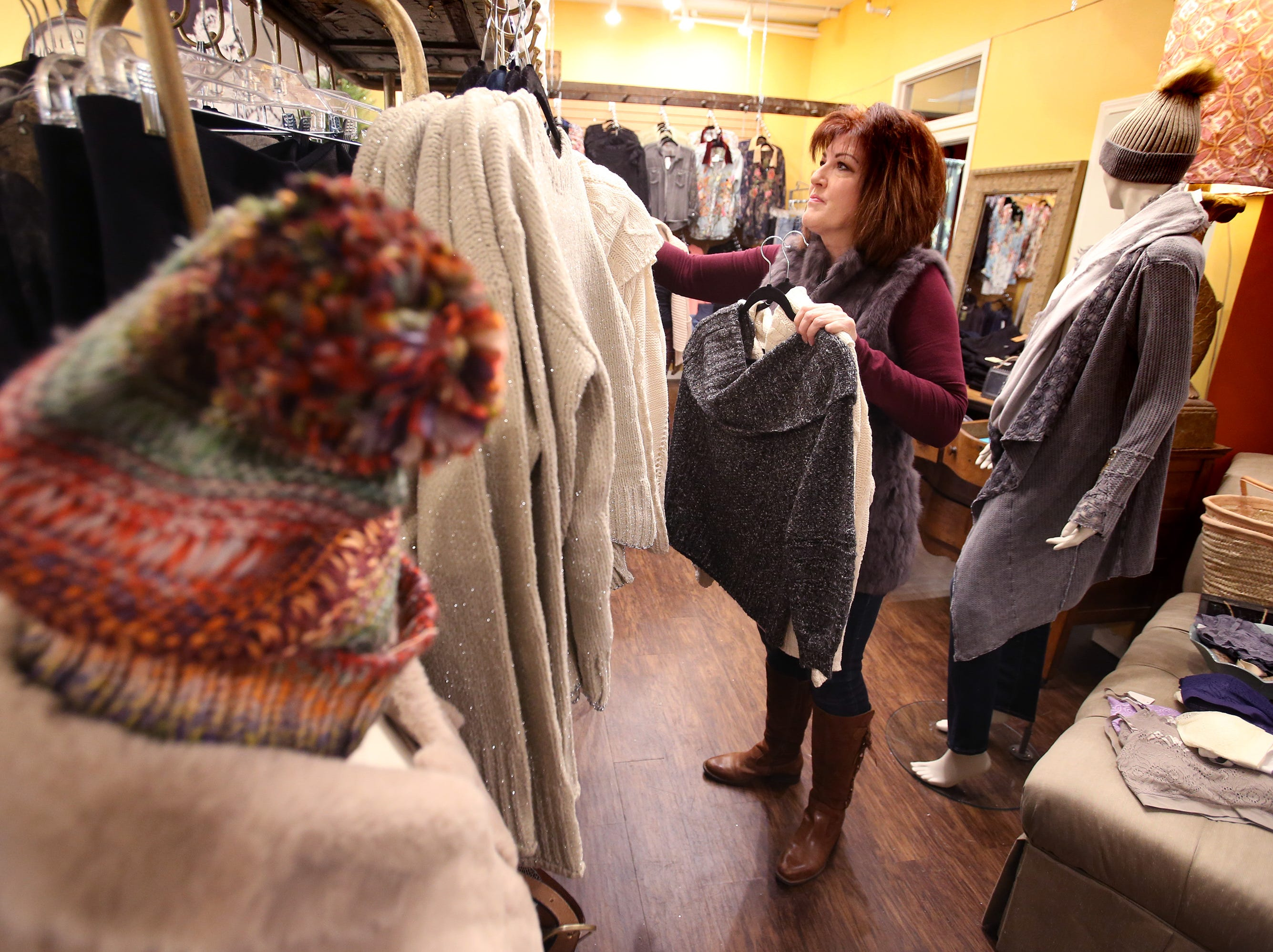 Kathy Keene, co-owner of Olive Branch Boutique at N88 W16598 Main St., resets the store's selection of women's clothing on Nov. 27 after a successful first weekend of the Christmas shopping season.