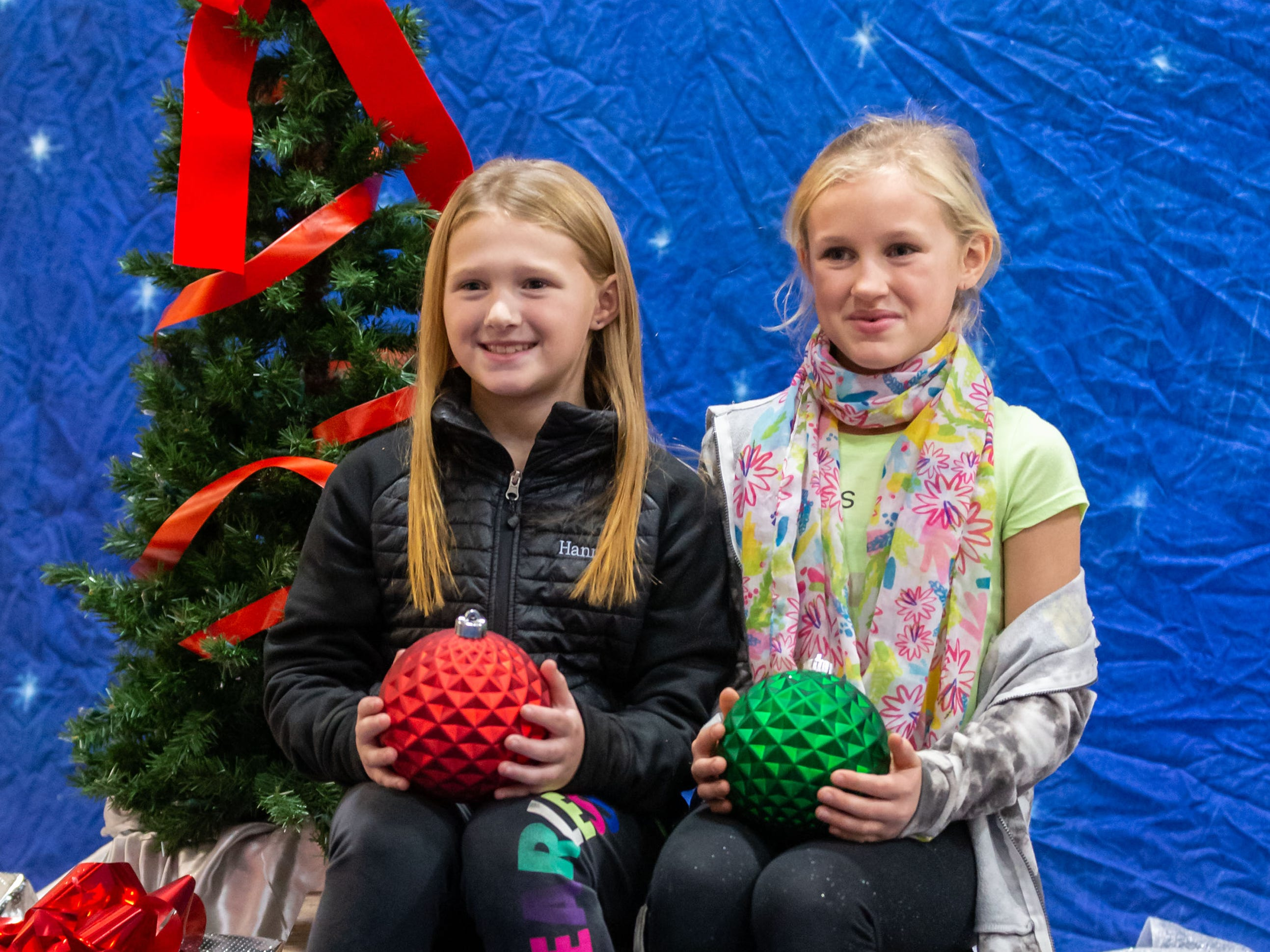 Hannah Ehr (left), 8, and Kara Kutz, 8, both of Cedarburg, pause for a holiday photo during Cedarburg's annual tree lighting ceremony at the Community Center on Monday, Nov. 26, 2018. The event, hosted by Cedarburg Chamber of Commerce, features make-and-take crafts, cookies, cider, music, caroling and a visit from Santa to light the tree.