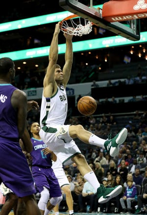 Bucks center Brook Lopez throws down a two-handed slam against the Hornets on Monday night.