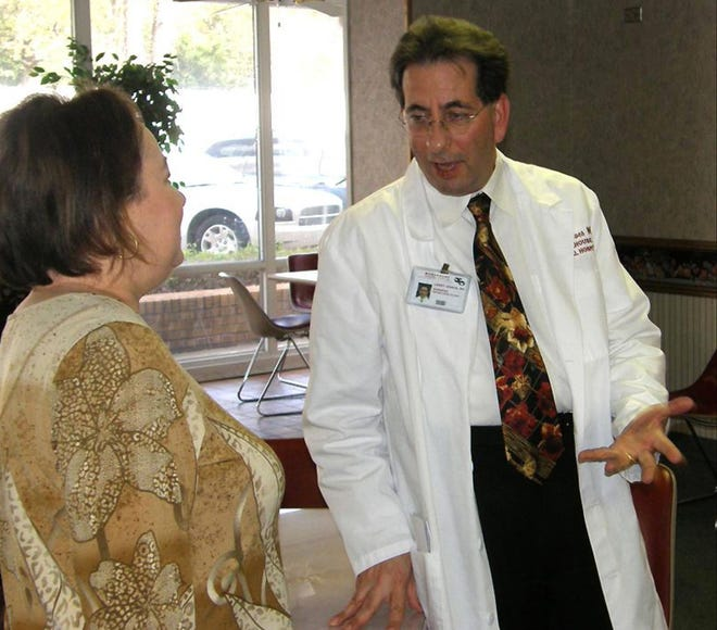Larry M. Isaacs, M.D. talks to his wife during an open house welcoming him to  Morehouse General Hospital in Basrop, Louisiana in 2012.