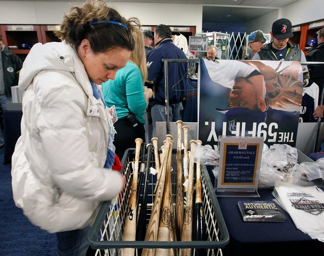 Kristin Schenk, of Milwaukee, looks over the used team bats for sale at a previous Brewers clubhouse sale.  Journal Sentinel Files