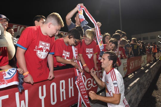 Red Bulls II midfielder Jared Stroud of Chester signs autographs after a match.