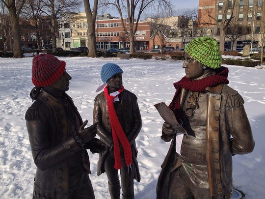 The mystery Morristown Fiber Fairies dressed up the statues of  Alexander Hamilton, l, Marquis de Lafayette and George Washington on the Morristown Green with hats and scarves as well as messages of giving for the needy. February 2, 2014, Morristown, NJ, Staff Photographer/Bob Karp MOR 0227 Fiber Fairy
