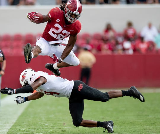 Alabama running back Najee Harris (22) leaps over Arkansas State defensive back Darreon Jackson (34) in second half action at Bryant Denny Stadium in Tuscaloosa, Ala., on Saturday September 8, 2018.