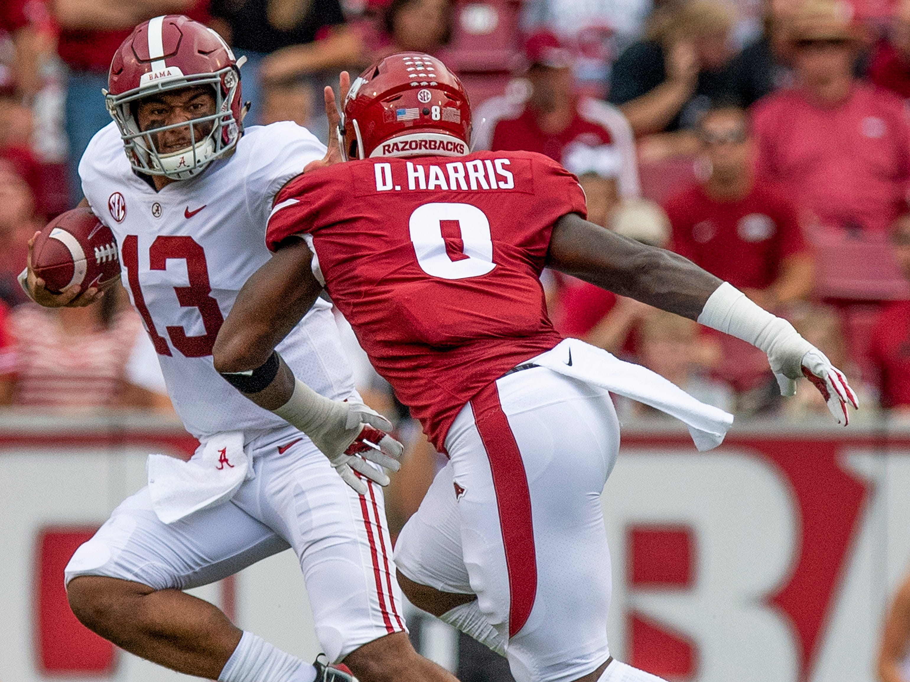 Alabama quarterback Tua Tagovailoa (13) tries to elude Arkansas linebacker DeÕJon Harris (8) during first half action in Fayetteville, Ark., on Saturday October 6, 2018.