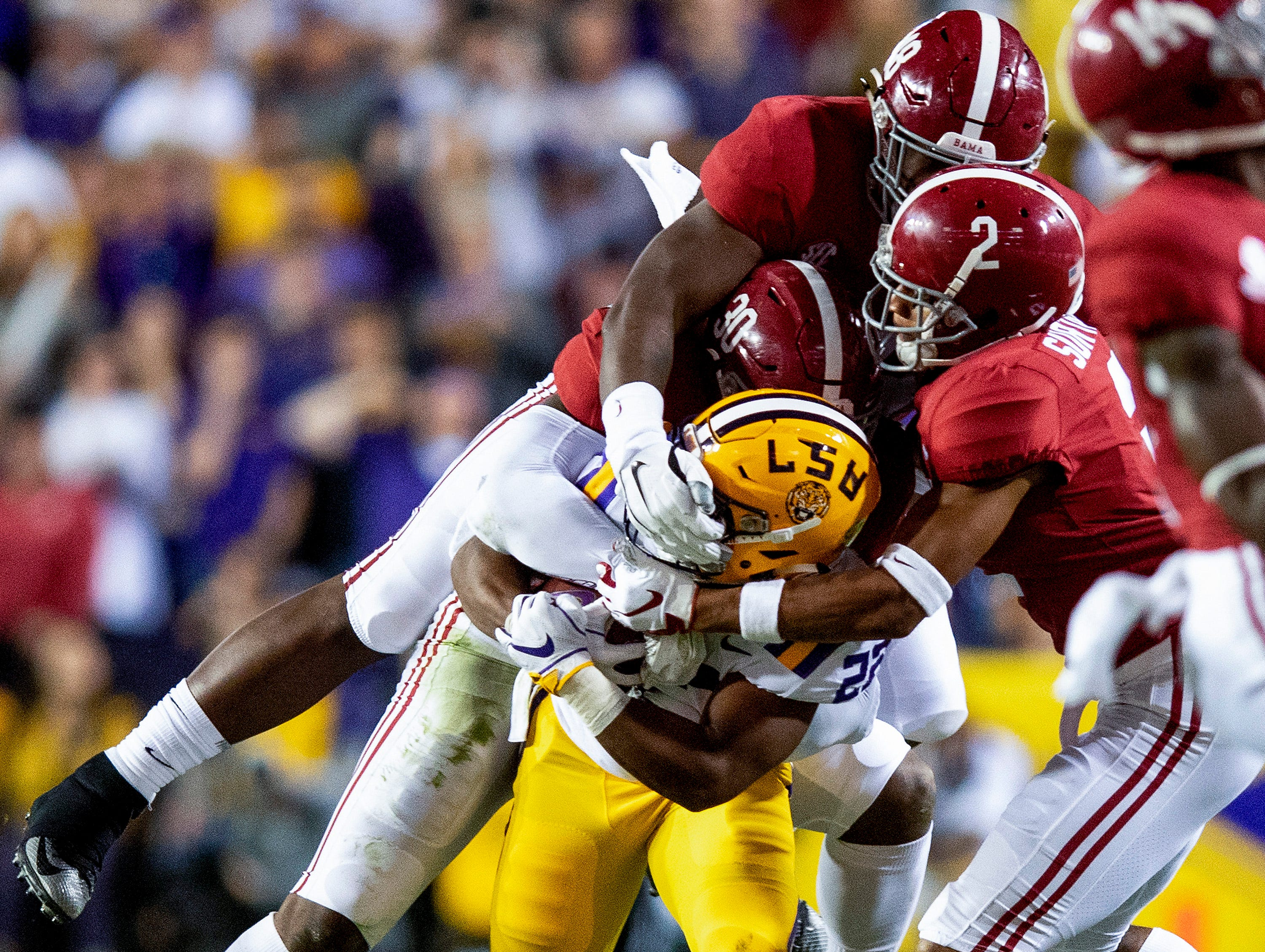 Louisiana State University running back Clyde Edwards-Helaire (22)  is tackled by Alabama linebacker Mack Wilson (30), defensive back Patrick Surtain, II, (2) and defensive lineman Phidarian Mathis (48) in first half action at Tiger Stadium in Baton Rouge, La., on Saturday November 3, 2018.