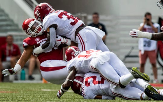 Alabama linebacker Dylan Moses (32), defensive back Patrick Surtain, II, (2) and defensive back Deionte Thompson (14) wrap up Arkansas tight end Cheyenne O'Grady (85) during first half action in Fayetteville, Ark., on Saturday October 6, 2018.