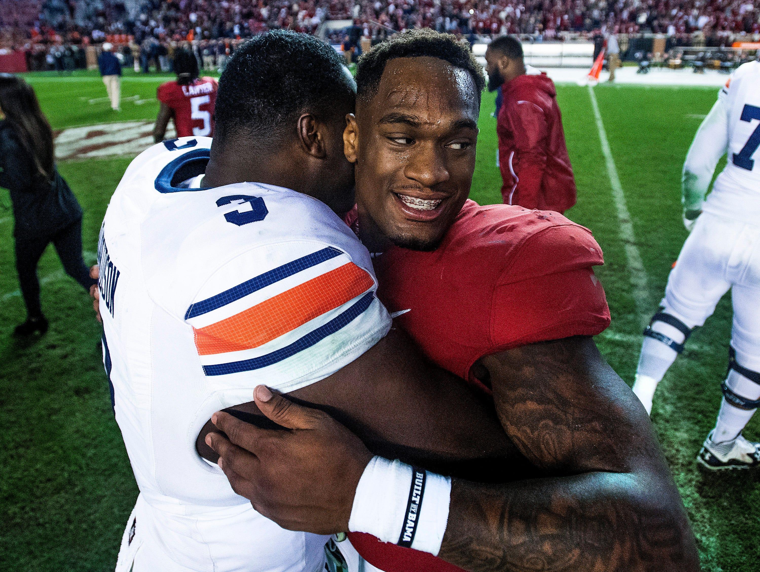 Alabama linebacker Mack Wilson (30) and Auburn defensive lineman Marlon Davidson (3) hug after the Iron Bowl at Bryant-Denny Stadium in Tuscaloosa, Ala., on Saturday November 24, 2018.