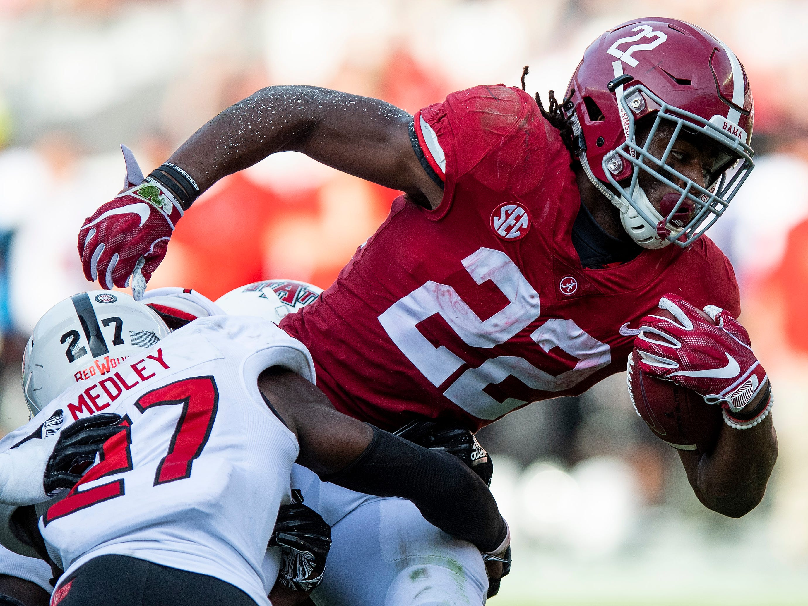Alabama running back Najee Harris (22) is stopped by Arkansas State defensive back Demari Medley (27) in second half action at Bryant Denny Stadium in Tuscaloosa, Ala., on Saturday September 8, 2018.