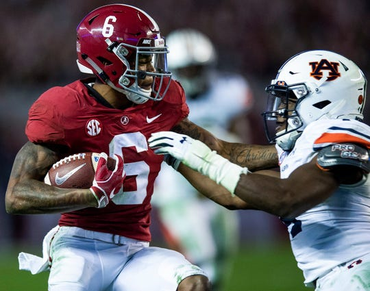 Alabama wide receiver DeVonta Smith (6) breaks the tackle of Auburn defensive back Noah Igbinoghene (4) to score a touchdown in second half action during the Iron Bowl at Bryant-Denny Stadium in Tuscaloosa, Ala., on Saturday November 24, 2018.