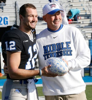 MTSU head football coach Rick Stockstill presents his son and MTSU quarterback Brent Stockstill a signed MTSU football as Brent Stockstill is honored with the other senior football players on Senior Day, before the start of the game against UAB at MTSU, on Saturday, Nov. 24, 2018.