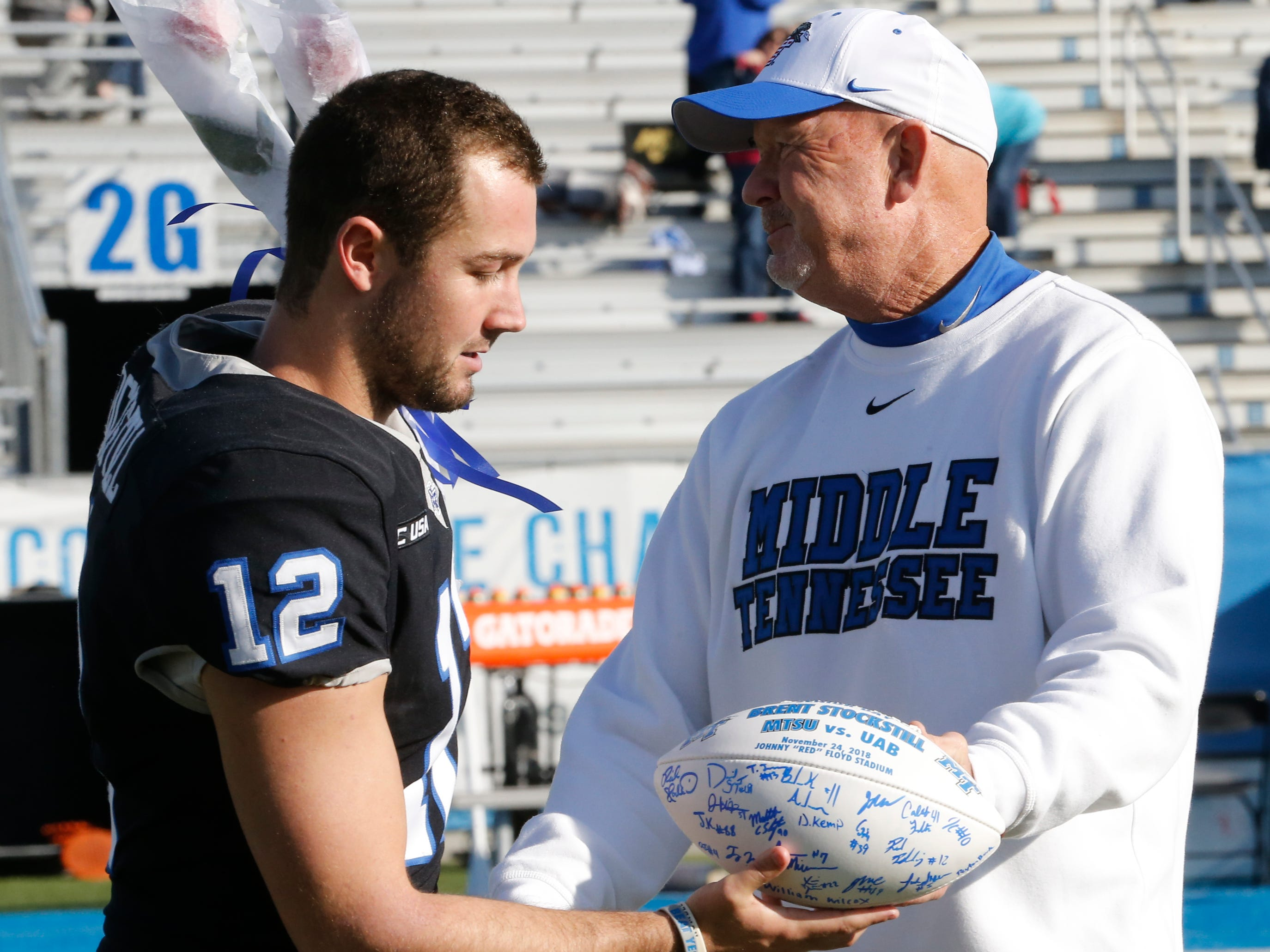 MTSU head football coach Rick Stockstill presents his on and MTSU quarterback Brent Stockstill a signed MTSU football as Brent Stockstill is honored with the other senior football players on Senior Day, before the start of the game against UAB at MTSU, on Saturday, Sept. 29, 2018.