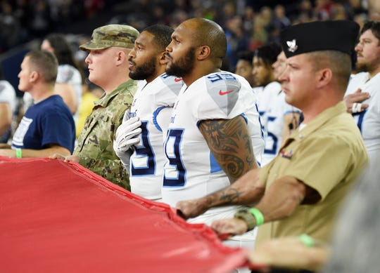 Titans linebacker Wesley Woodyard (59) and defensive tackle Jurrell Casey (99) stand with military personnel as they hold the flag during pregame ceremonies at NRG Stadium Monday, Nov. 26, 2018, in Houston, Texas.