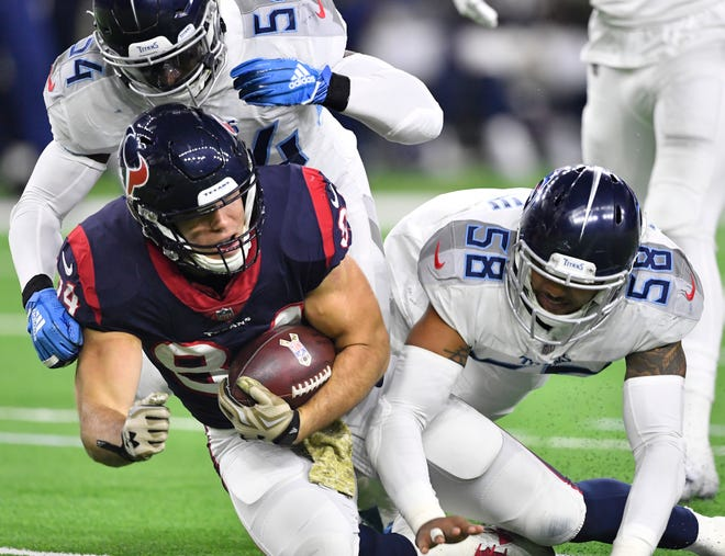 Texans tight end Ryan Griffin (84) gets a first down past the Titans defense in the fourth quarter Monday.