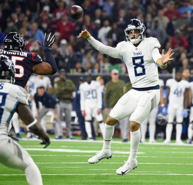 Titans quarterback Marcus Mariota (8) throws under pressure to running back Dion Lewis in the second quarter Monday.