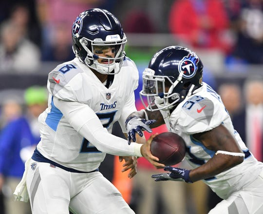 Titans quarterback Marcus Mariota (8) hands off to running back Dion Lewis (33) in the second quarter at NRG Stadium Monday, Nov. 26, 2018, in Houston, Texas.