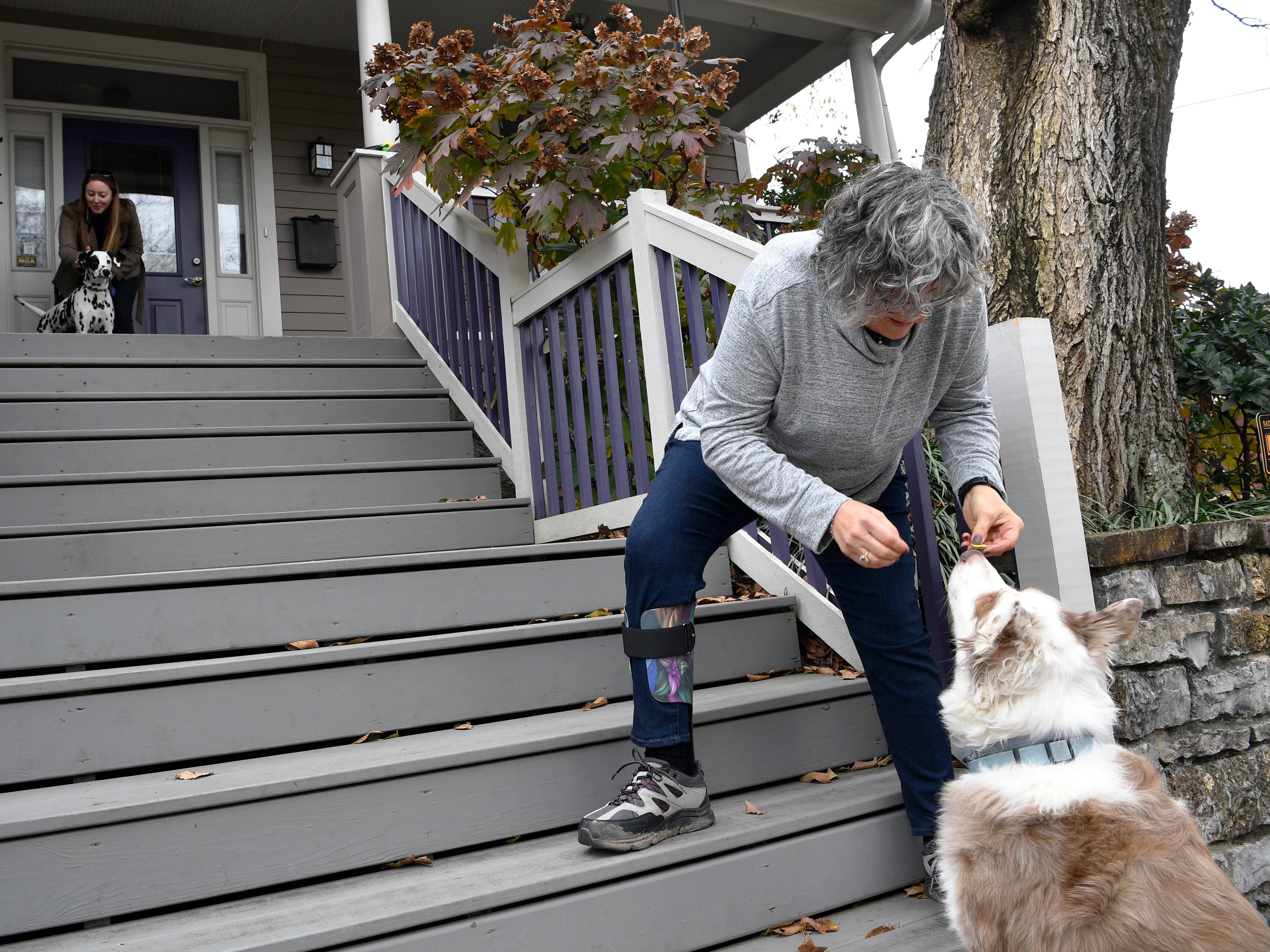 "Sheila Cope gives a treat to Bama, who is blind but knows when he is at her house. Cope runs the popular Instagram account ""Dogs of Germantown"" and has documented over 150 dogs that have passed by her door."
