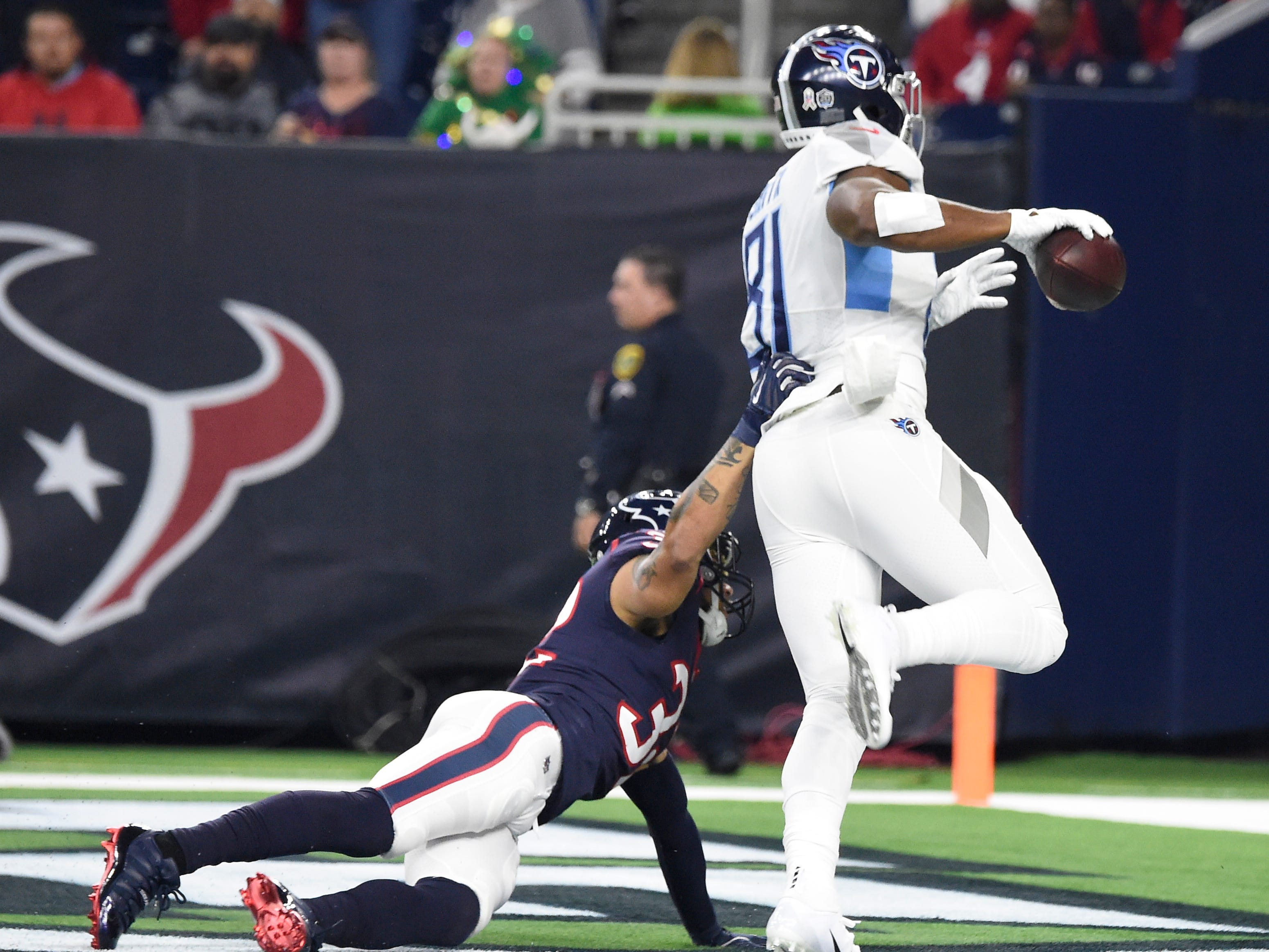 Titans tight end Jonnu Smith (81) pulls away from a Texans defender to score the team's first touchdown in the first quarter at NRG Stadium Monday, Nov. 26, 2018, in Houston, Texas.